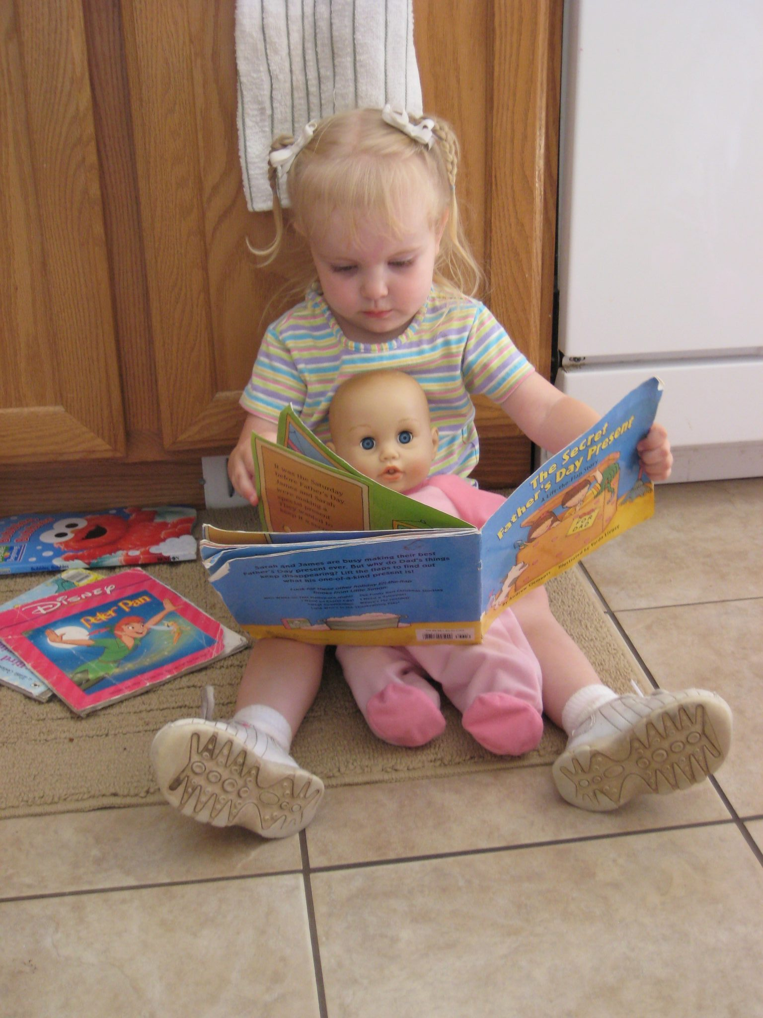 Child Reading Book to Doll